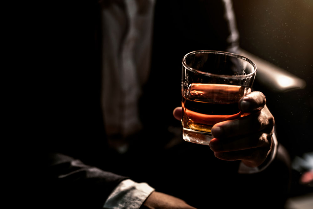 Man holding glass with alcohol content
